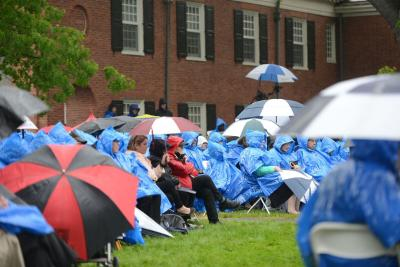 Attendees hold umbrellas
